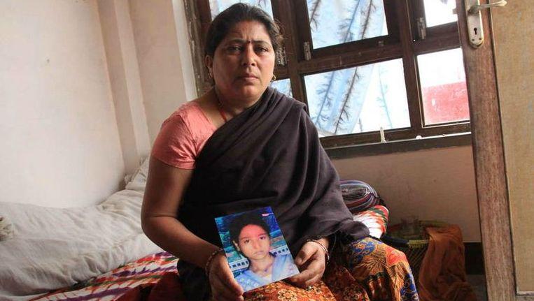 Een Nepalese moeder toont een foto van haar afwezige zoon. Beeld Arletta Andre