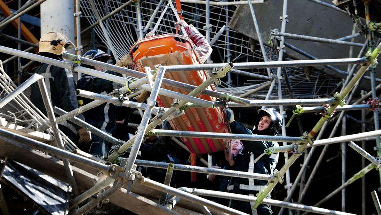 Gewonde bouwvakker wordt per brancard naar beneden gehaald. Beeld anp