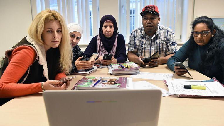 Cursisten van verschillende komaf doen een oefening met de laptop en hun mobiele telefoon bij een inburgeringscursus Beeld Marcel van den Bergh
