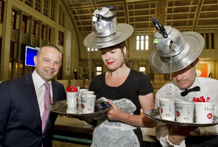 Financieel topman Michel Cup krijgt een kop thee ingeschonken door een actrice, nadat hij op de Amsterdamse beurs officieel het startsein heeft gegeven voor de optiehandel in D.E Master Blenders 1753-aandelen. Beeld anp