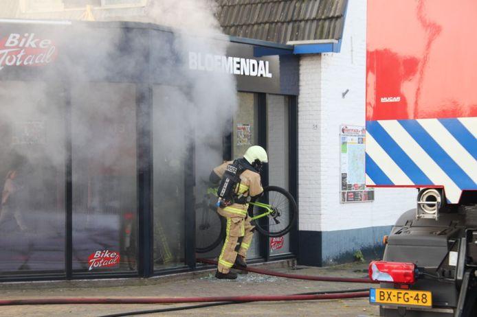 De brandweer haalt de fietsen uit de winkel in Holten.