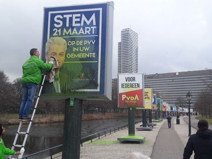 Groep de Mos-raadslid Arjen Dubbelaar poetst het PVV-bord bij het Malieveld.