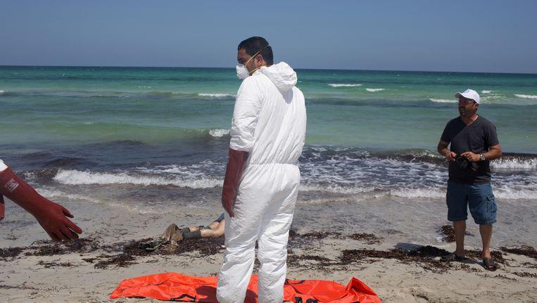 Reddingswerkers bergen de lichamen van verdronken vluchtelingen op het strand in Libië. Beeld ap