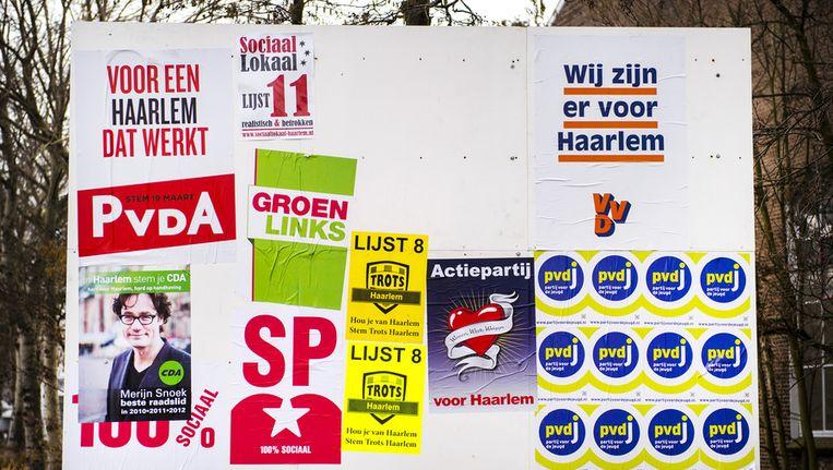 Een bord met affiches van politieke partijen die deelnemen aan de gemeenteraadsverkiezingen 2014 langs de openbare weg in Haarlem. Beeld anp