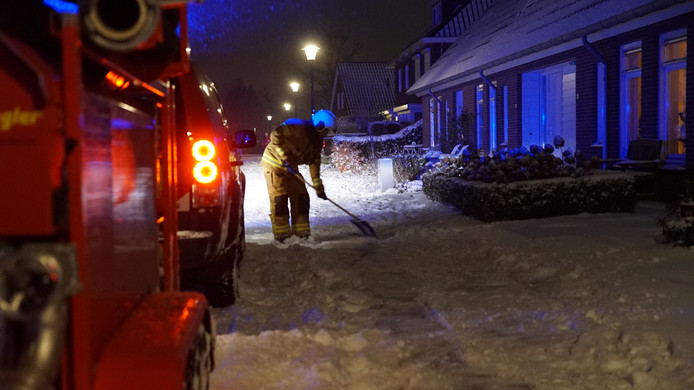 Een lid van het brandweerkorps in de sneeuw op zoek naar de waterput.