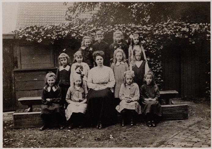 De tweede klas van de Openbare Lagere School voor Meisjes in Plantsoen-Zuid in 1918. Het meisje rechts van juffrouw de Looze is Nel Pierik, die illegale nieuwsberichten voorlas.