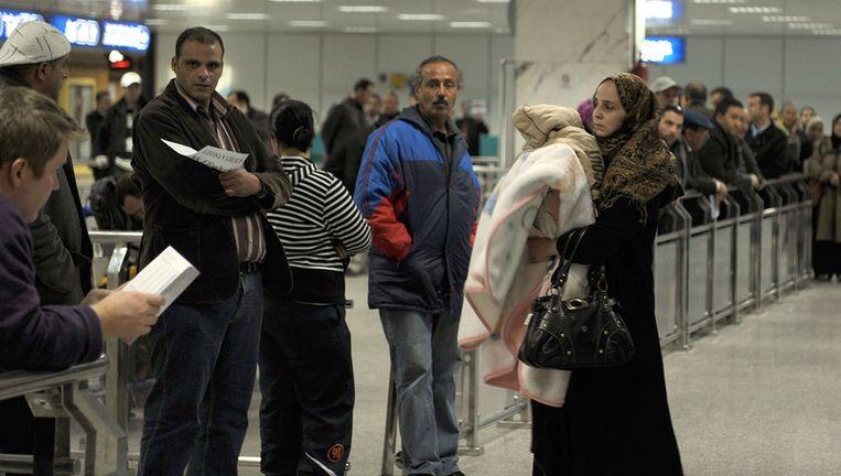 Een Tunesische vrouw arriveert op het vliegveld van Tunis. Samen met circa 2.300 andere Tunesiërs die in Libië woonden, is zij het land ontvlucht. © afp Beeld
