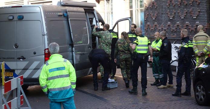 Medewerkers van de EOD en de politie bij het busje waarin de granaat werd afgevoerd.