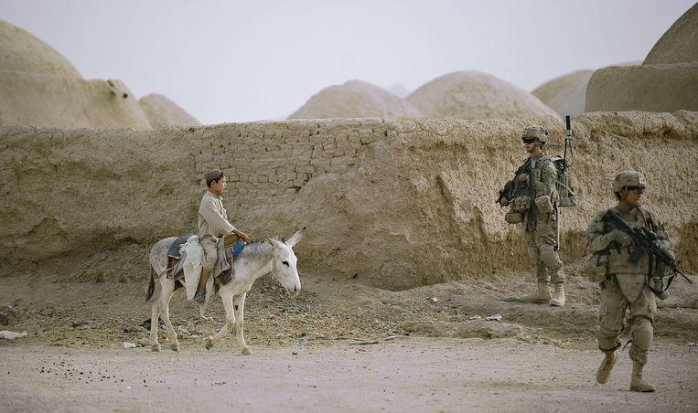 An Afghaanse jongen rijdt met zijn ezel langs de Amerikaanse militairen in de Zuidelijke provincie Kandahar, 2012.  Beeld AFP