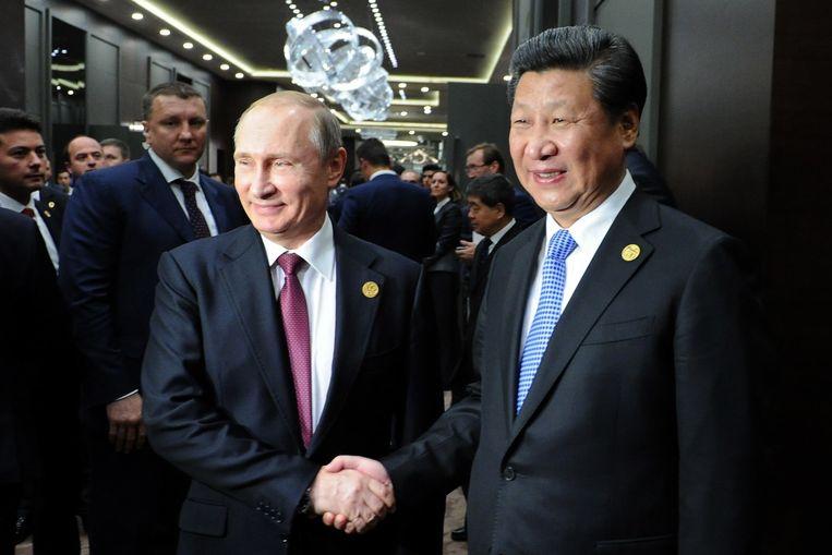 De Russische president Poetin schudt handen met de Chinese president Xi Jinping. Beeld anp