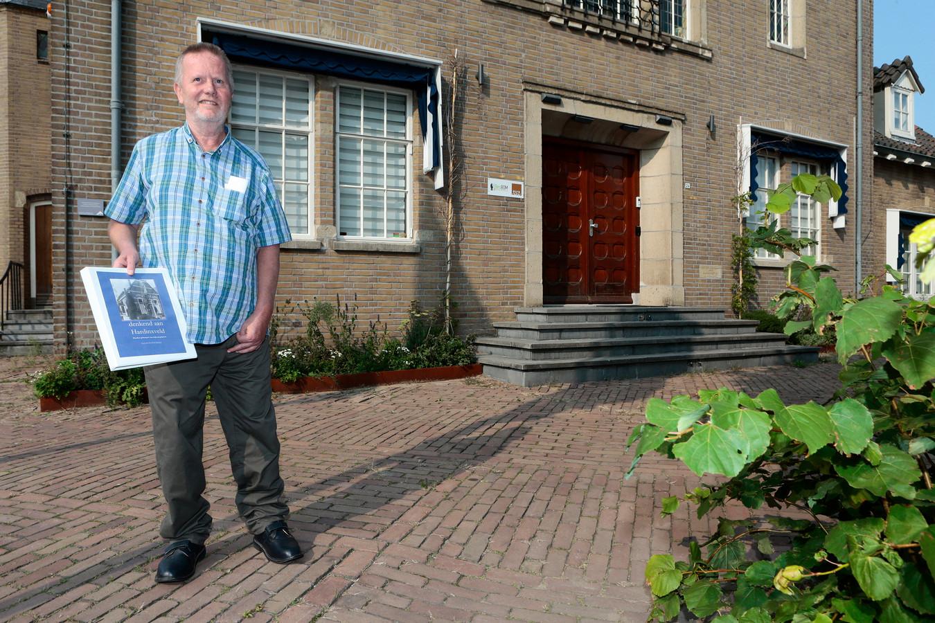 Leen van den Herik voor het oude gemeentehuis. Het boekje dat hij schreef, is gratis verkrijgbaar.