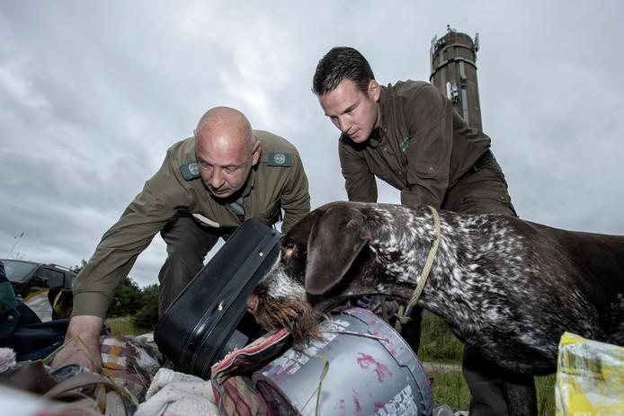 Boa Brabants Landschap Philip Oprel (l) en Boswachter Erik de Jonge met hond onderzoeken achtergelaten spullen aan de bosrand