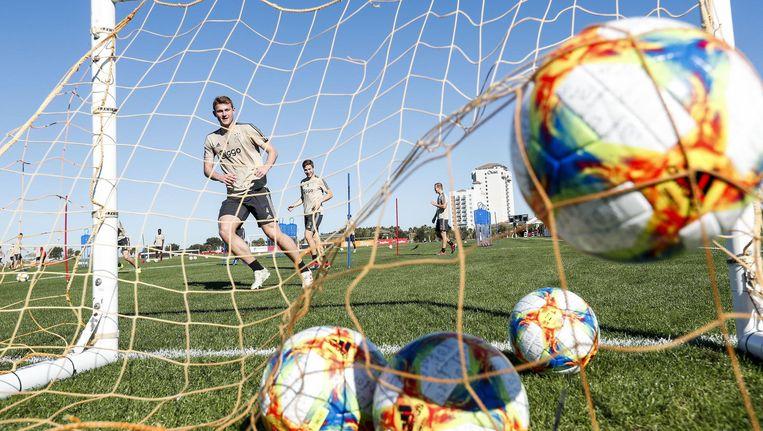 Onder een stralende hemel kijkt Carel Eiting toe hoe Matthijs de Ligt een bal in een van de doeltjes schiet op het trainingsveld in Orlando. Beeld Maurice van Steen/Vi Images