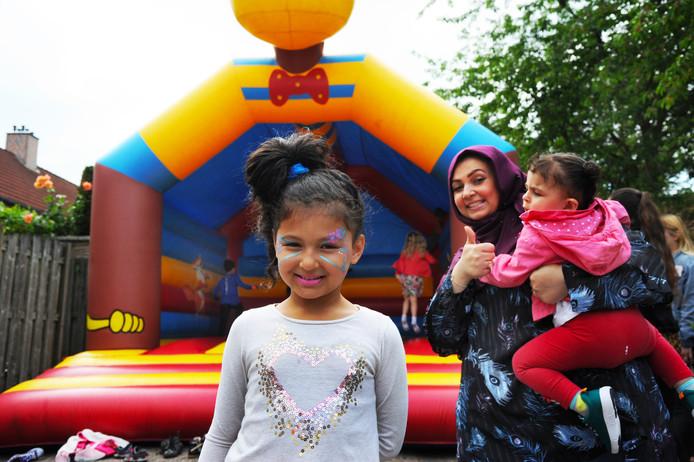 Het is feest in de Edelstenenbuurt ter gelegenheid van een groot renovatieproject.  Angim , Randa en Zahwai (vlnr) vermaken zich bij het springkussen.