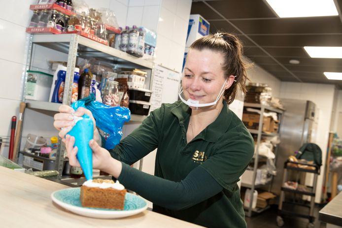 Medewerkster Fieke de Ruiter legt de laatste hand aan een stuk carrotcake in lunch- en ijsroom spIJS in Warnsveld.