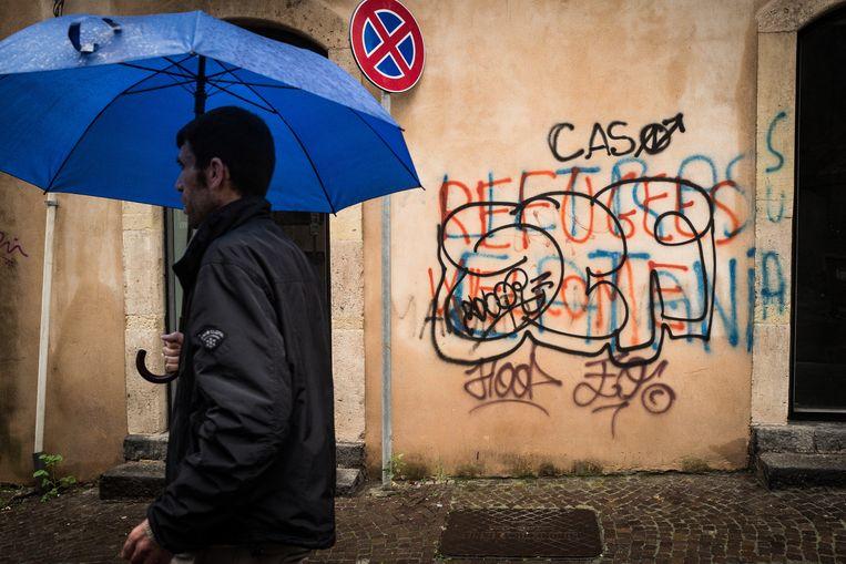'Refugees Welcome' staat er op een muur in Catania gekalkt.  Beeld Nicola Zolin