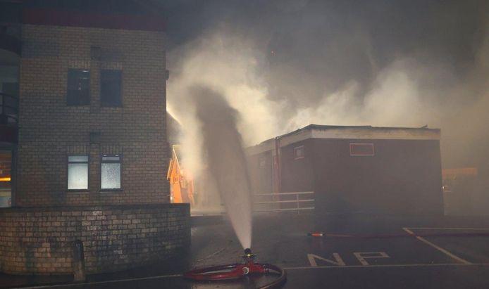 Brandweer druk doende met het blussen van de kleedkamers.