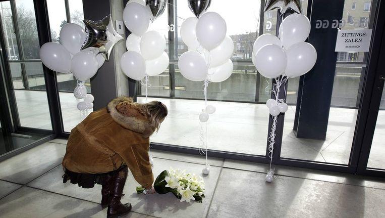 Een vrouw legt bloemen neer bij het Paleis van Justitie in Gent. De balonnen representeren de slachtoffers van De Gelder. Beeld afp