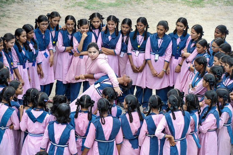 Syeda Falak, karatekampioen van India en moslima, demonstreert zelfverdedigingstechnieken aan een groep leerlingen van de Telangana Minority Residential-meisjesschool in Hyderabad. De TMREIS-scholen zijn vier jaar geleden opgericht om kansarme kinderen van minderheden aan een goede opleiding te helpen.   Beeld AFP