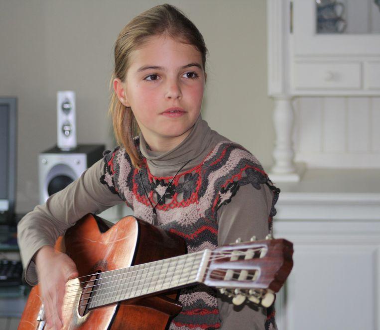 De 11-jarige Ine tokkelend op de gitaar die ze van Peter Van Laet kreeg
