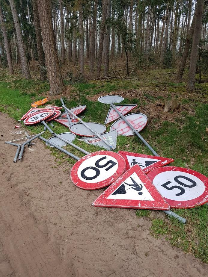 De lading die bestond uit verkeersborden werd gedumpt langs een zandweg.