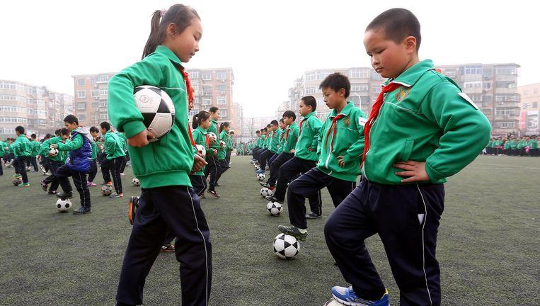 Chinese scholieren van de Yinxingbu-basisschool in Tianjin doen hun oefeningen op het vierde Campus Voetbal en Cultuur Festival in hun stad. Beeld Hollandse Hoogte