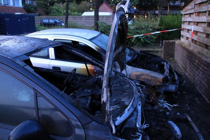 De twee uitgebrande auto's aan de Aalbeek in Ede.