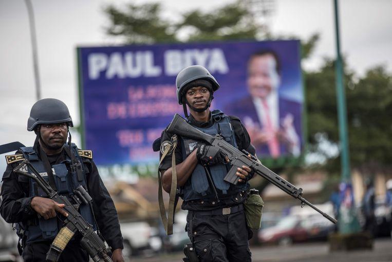 Zwaar bewapende politiemannen patrouilleren in de stad Buea in het Engelse deel van Kameroen. Op de achtergrond een foto van president Paul Biya, die nu een conferentie houdt over de burgeroorlog in zijn land.  Beeld MARCO LONGARI, AFP