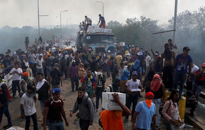 Oppositieleden halen een in brand gestoken vrachtwagen met hulpgoederen leeg bij de Francisco de Paula Santander brug  op de grens tussen Colobia en Venezuela. De brand ontstond na schermutselingen met het leger.