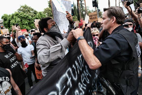 Zo kan het ook: een agent schudt een demonstrant de hand in Los Angeles. Een Een meerderheid van de Amerikanen sympathiseert met de landelijke protesten in de VS. Dat blijkt uit enquête die door marktonderzoeksbureau Ipsos is uitgevoerd in opdracht van persbureau Reuters.