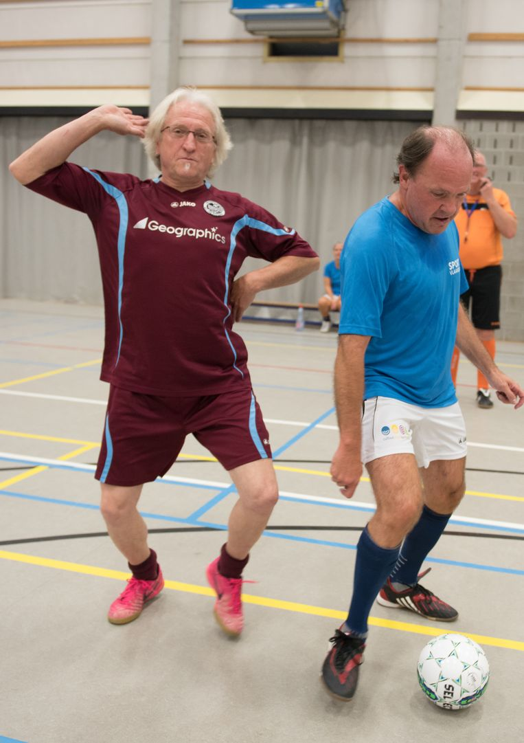 Marc de Bel maakt een gekke move terwijl minister Muyters de bal aan de voet houdt.