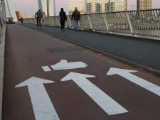 Asofietsers Erasmusbrug buigen voor boegeroep en pijlen op de weg
