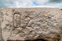 Code in de stenen die in 1900 moest helpen bij het in elkaar zetten van het monument. Het ronde plaatje rechtsboven heeft dezelfde code.