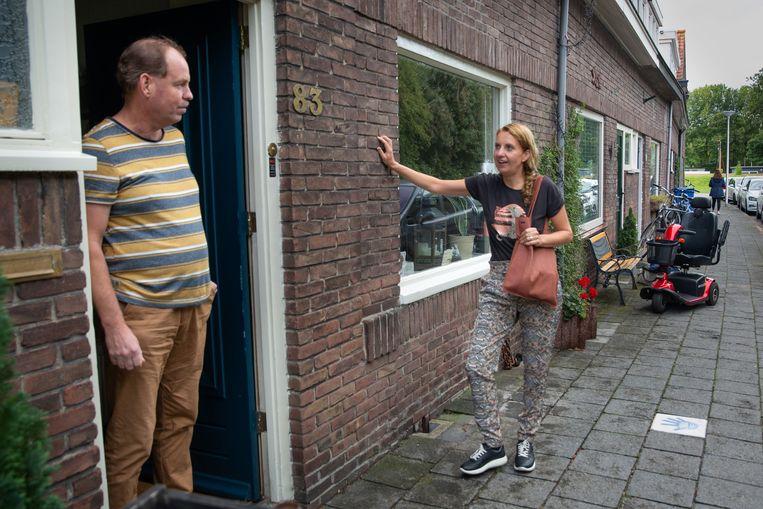 Corinne Tijsseling praat met Sjaak Schuurhuis, bij wie een zwaaisteen voor de deur ligt. 'Door die tegel hinkelde er steeds een buurmeisje voor mijn raam langs.' Beeld Herman Engbers