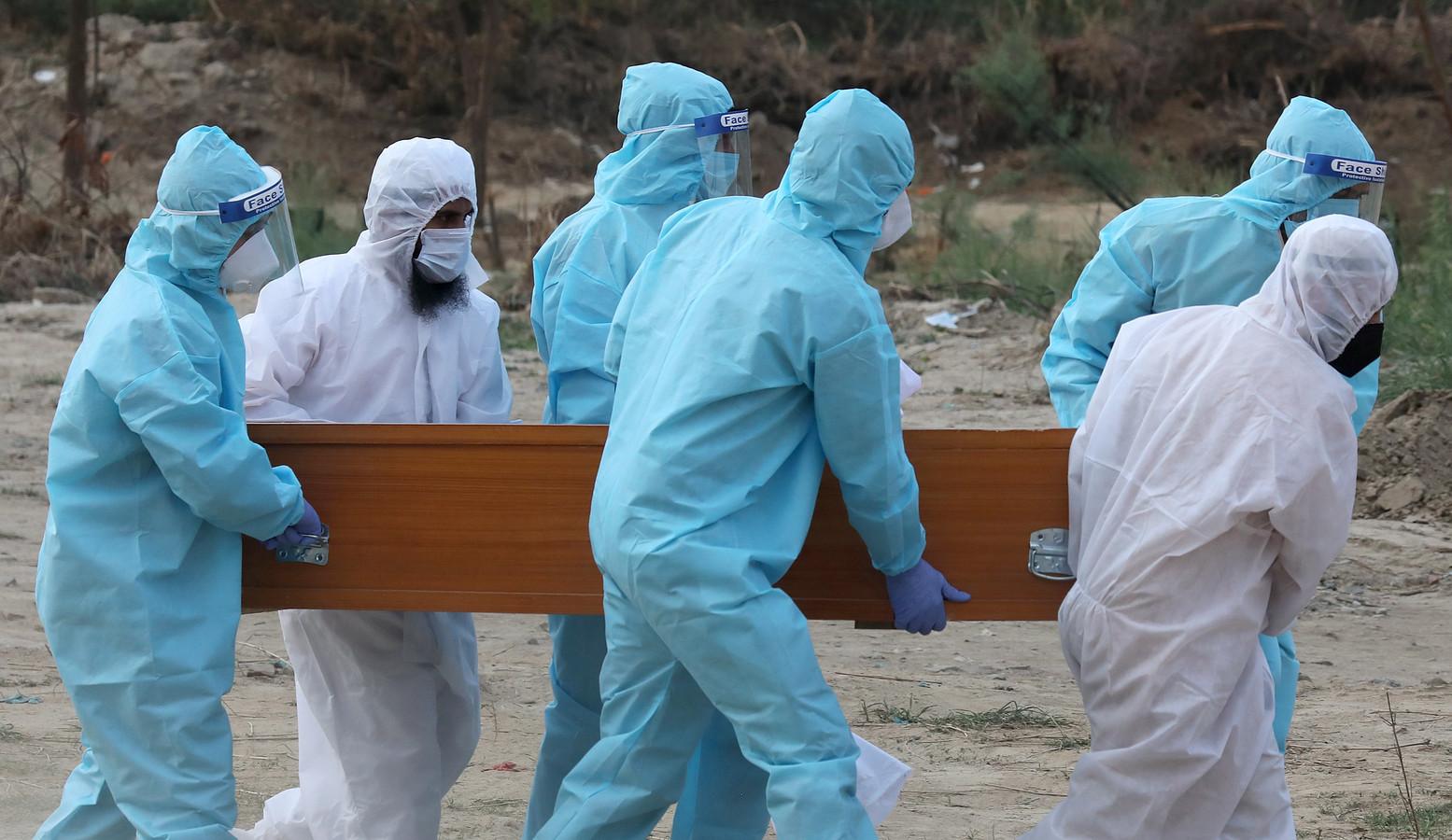 Familieleden in beschermende kledij brengen een aan Covid-19 gestorven familielid naar zijn laatste rustplaats in New Delhi, India.