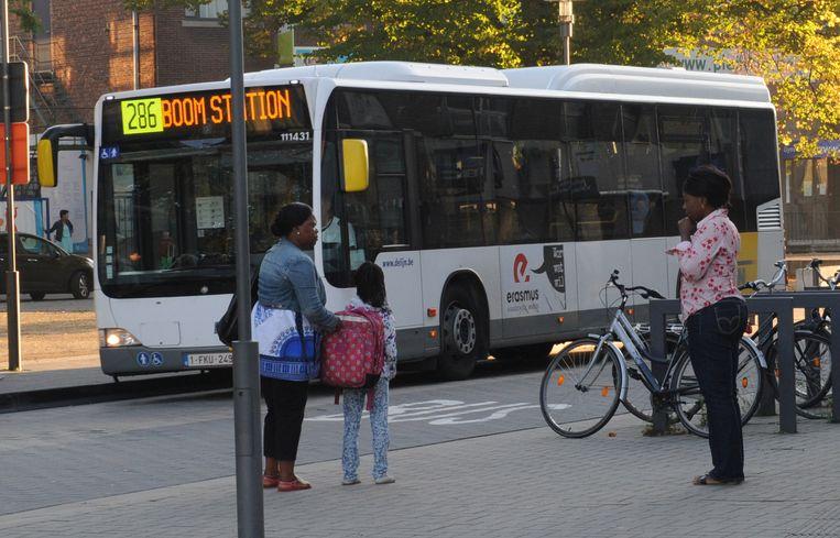 Een mama vergezelt haar kind op weg naar de bushalte.