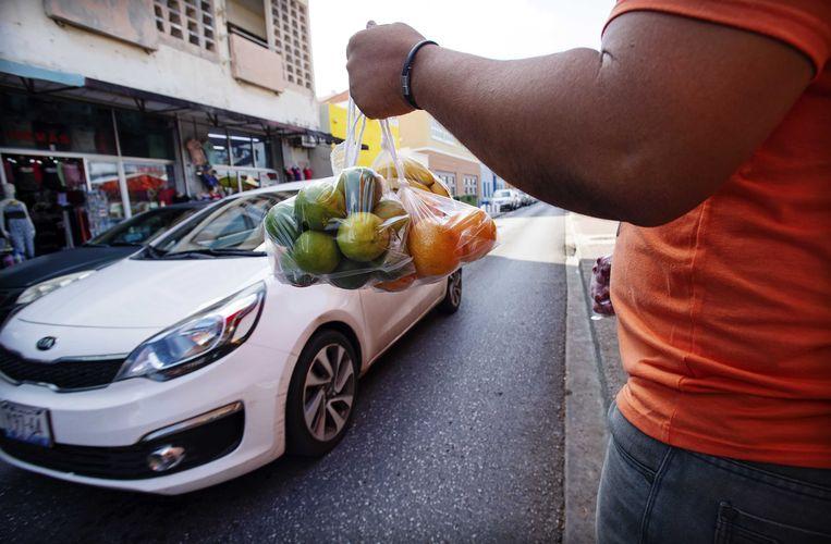 Venezolaanse kooplui verkopen fruit op de floating market in de wijk Punda in het centrum van Willemstad. Op deze markt verkopen Venezolanen vers waar, die ze met de bootjes die liggen aangemeerd over brengen van het vaste land. Veel marktkraampjes zijn gesloten vanwege het exportverbod door de crisis in Venezuela.  Beeld ANP