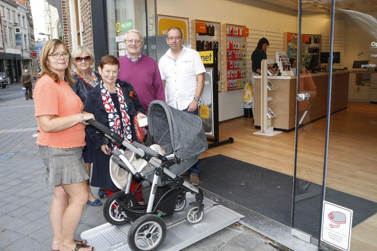 Marleen (links) toont hoe ze met haar kinderwagen via de oprijplaat makkelijk de winkel kan binnenrijden. Naast haar staan Paul Rabay, Agnes Deroost, Leona Cloots en Patrick Vanderveken van Toegankelijk Tienen.