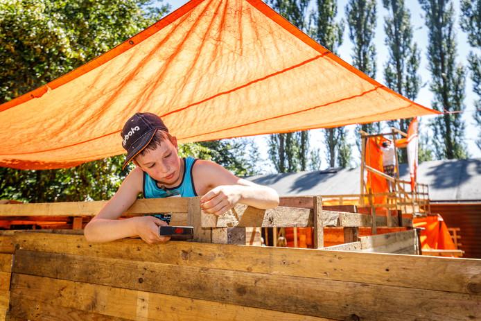 Bij de Huttenbouwweek in Emmeloord hangen kinderen zeilen om voor schaduw.