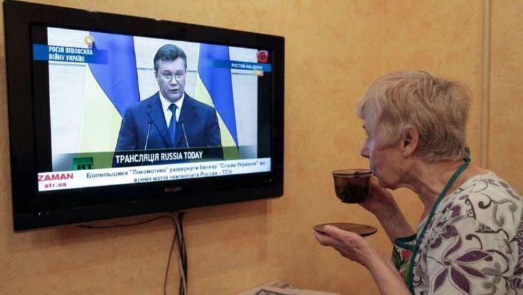 Een vrouw op de Krim bekijkt via de Russische tv een persconferentie van de verdreven Oekraïense president Janoekovitsj. Beeld epa