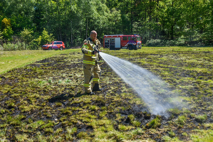 De brandweer blust het vuur in het weiland bij Oosterbeek.