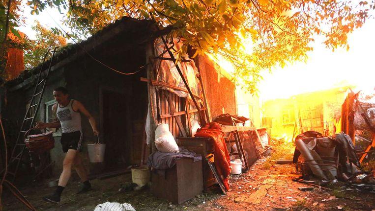Een Oekraïense man haalt zijn eigendommen uit zijn woning in de buurt van Donetsk na gevechten tussen separatisten en het Oekraïense leger. Beeld afp