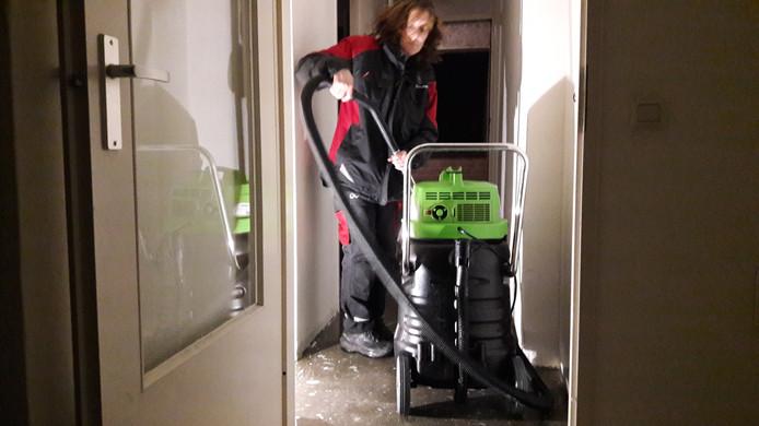 Een medewerkster van Dolmans Calamiteiten zuigt het water weg in het bovenste appartement.