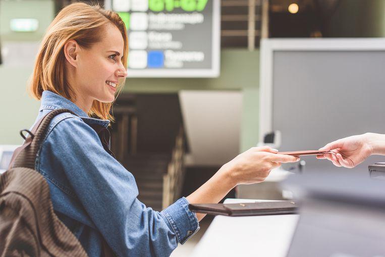 Een vrouw krijgt haar ticket op de luchthaven.