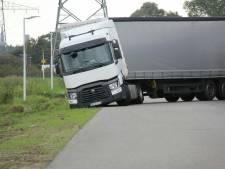 Vrachtwagen uit Litouwen vast in de berm na te wijde bocht in Borne