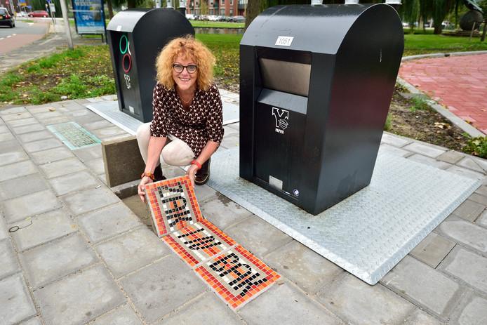 Jeanette Nieuwesteeg legt mozaiektegels bij vuilcontainers met teksten als 'zak in bak' en 'geen los vuil'.