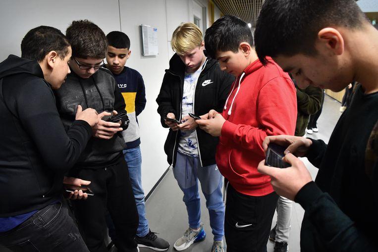 Leerlingen van het Melanchthon zitten in de pauze op hun smartphone.  Beeld Marcel van den Bergh / de Volkskrant
