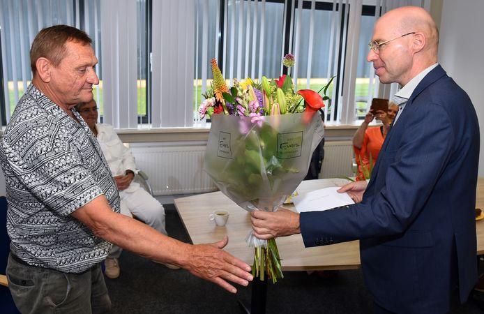 Jan-Henk Janssen, directeur van Laborijn, geeft bloemen aan Hendrik-Jan Teeuwsen, die bijna 49 jaar voor de sociale werkplaats werkt.