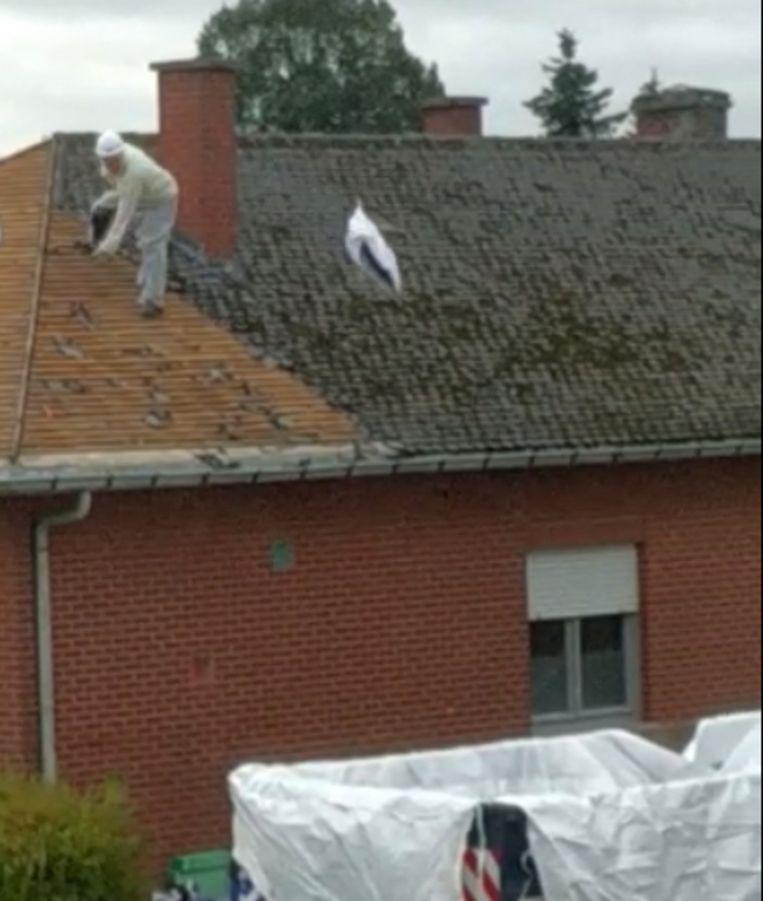 Arbeider gooit zak met stukken dakbedekking in een container.