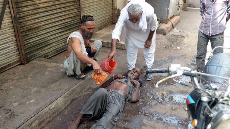 Pakistaanse mannen helpen elkaar om afkoeling te vinden in de stad Karachi.